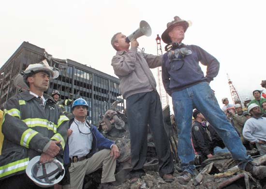 Original caption: U.S. President George W. Bush addresses a crowd as he stands with retired firefighter Bob Beckwith (R) from Ladder 117 at the scene of the World Trade Center disaster in New York, September 14, 2001. The World Trade Center Towers and 7 World Trade Center were destroyed after both the landmark towers were struck by two hijacked planes in a terror attack on September 11.  REUTERS/Win McNamee September 14, 2001